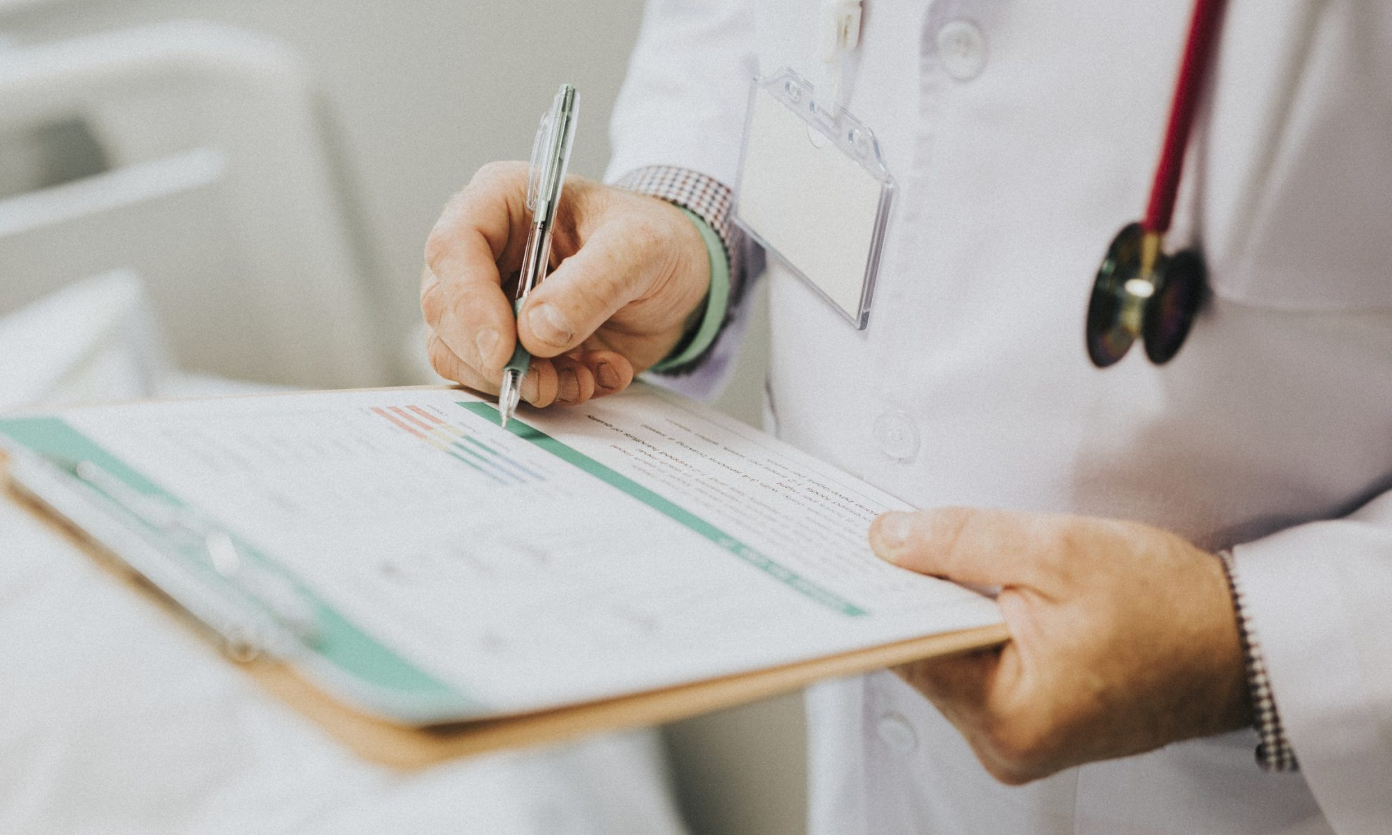 Doctor in lab coat with stethoscope writing on medical chart in clipboard